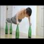 בן שבע עושה שכיבות שמיכה על בקבוקים